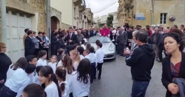 Il nuovo arcivescovo festeggia in piedi su una Porsche trainata da 50 bambini: è polemica -VIDEO-