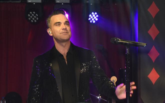 Robbie Williams tocca i fan e si disinfetta le mani
