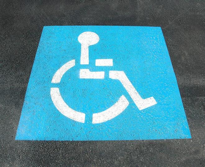 Parcheggia Ferrari su posto riservato e aggredisce padre di disabile